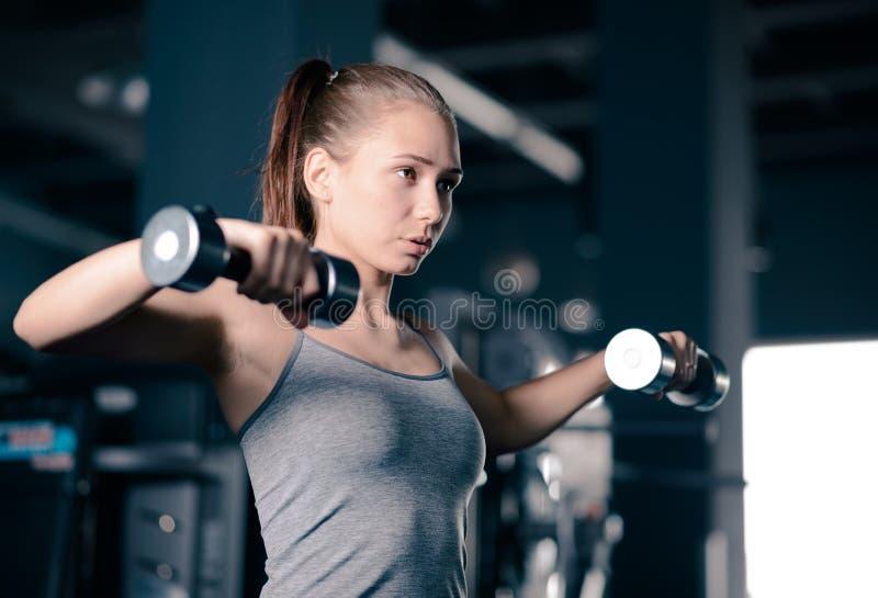 Attraktive junge Sport-Frauen-anhebende Dummk?pfe in der Turnhalle Eignung und gesunder Lebensstil lizenzfreie stockfotos