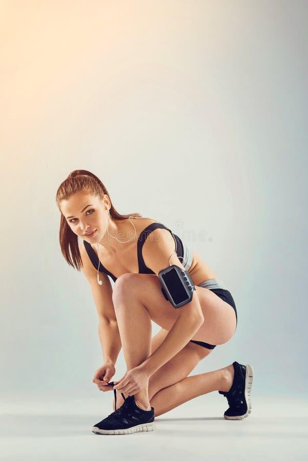 Attraktive junge Sportlerin, die ihre Schnürsenkel bindet stockfotos