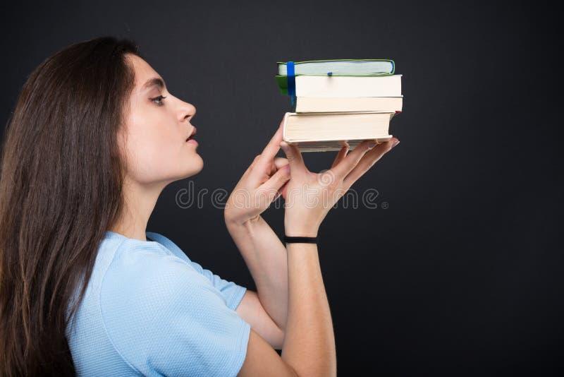 Attraktive junge Studentin, die ihre Bücher zählt stockbild
