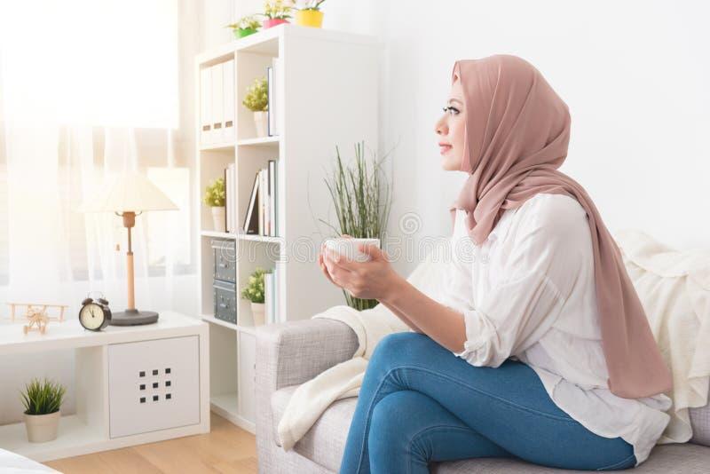 Attraktive junge weibliche moslemische haltene Kaffeetasse stockfotografie