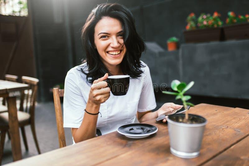 Attraktive kaukasische Frau mit dem angenehmen netten Lächeln, das am Terrassencafé, an trinkendem Kaffee sitzt und online genieß stockbilder