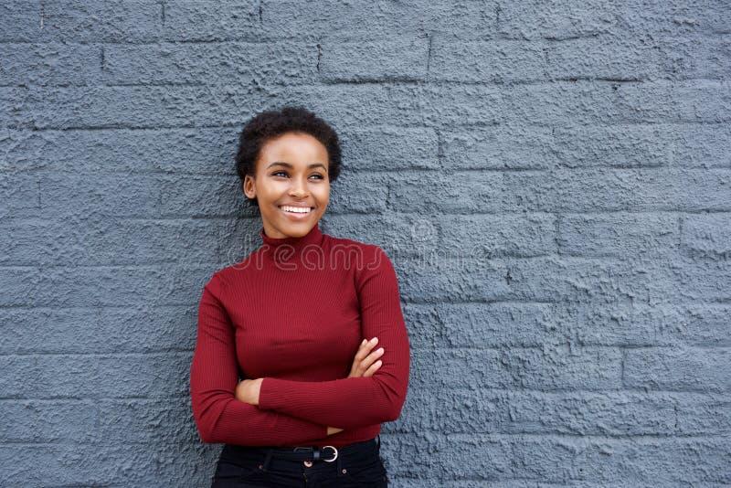 Attraktive lächelnde afrikanische Frau, die an der grauen Wand sich lehnt lizenzfreie stockfotos