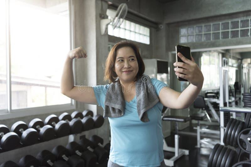 Attraktive lächelnde aktive Eignung der älteren asiatischen Frau in der Turnhalle und im Nehmen eines selfie, das Muskel zeigt lizenzfreies stockfoto