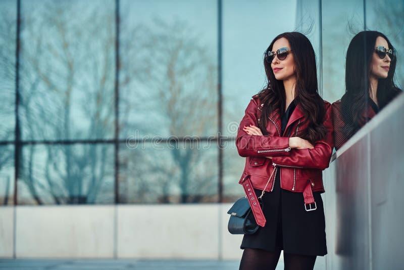 Attraktive lächelnde Frau in der roten Jacke und in der Sonnenbrille wirft nahe Glasgebäude auf stockbilder