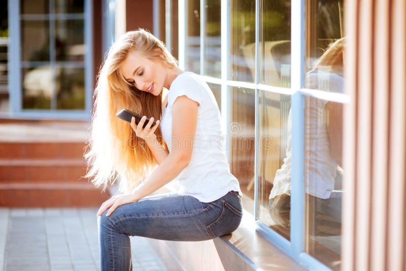 Attraktive lächelnde Frau, die draußen Smartphone verwendet lizenzfreie stockbilder