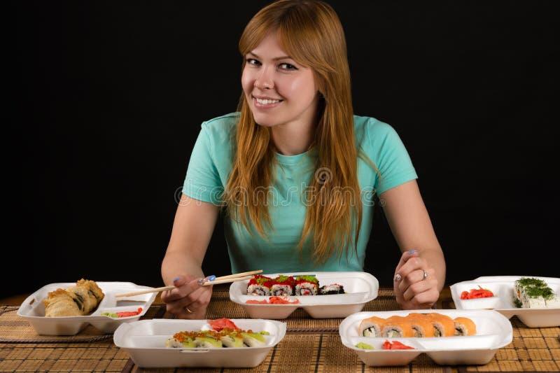 Attraktive lächelnde Frau, die am Tisch mit Rollen sitzt lizenzfreies stockbild