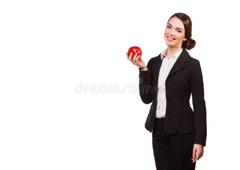 Attraktive lächelnde Geschäftsfrau, die den roten Apfel, lokalisiert auf Weiß hält lizenzfreie stockbilder