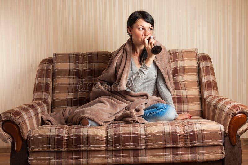 Attraktive lächelnde junge Frau, die auf dem Sofa sich entspannt stockfoto