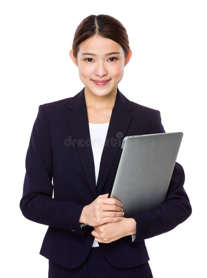 Attraktive lächelnde junge Geschäftsfrau, die Laptop-Computer hält stockfotos