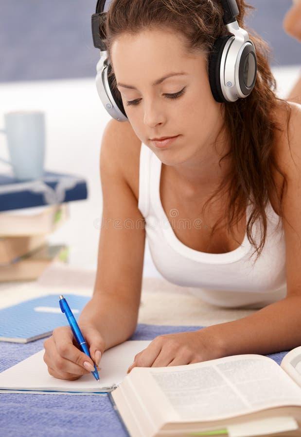 Attraktive Mädchenschreibensheimarbeit, die auf Fußboden legt stockbild
