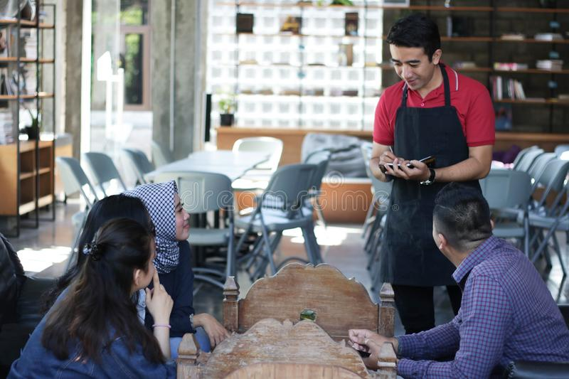 Attraktive männliche Kellnerstellung, welche die Aufträge am Café und am Restaurant von der Gruppe des jungen glücklichen Freunds lizenzfreie stockfotografie