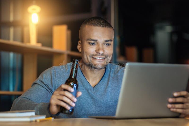 Attraktive männliche Person, die seinen Laptop verwendet lizenzfreie stockfotos