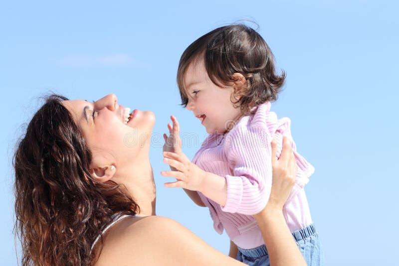 Attraktive Mama, die ihre Tochter aufzieht und zusammen spielt stockbild