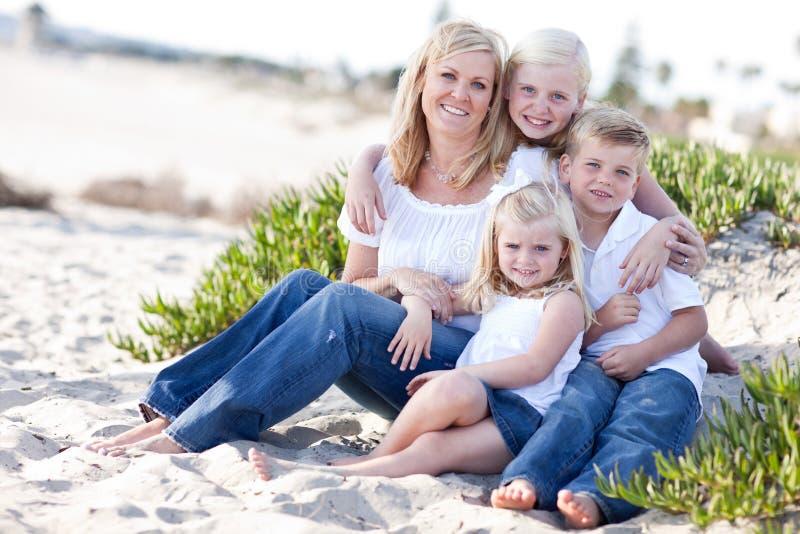 Attraktive Mamma und ihre netten Kinder am Strand lizenzfreie stockbilder