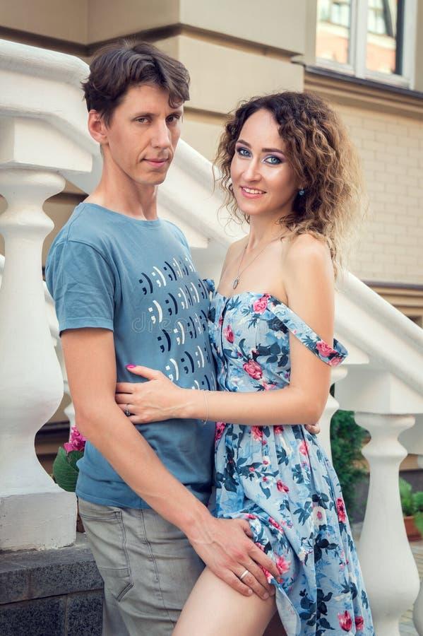 Attraktive Mannumarmungen und -anschläge seine schöne Freundin Ein Paar betrachtet die Kamera Alte Straße im Hintergrund lizenzfreies stockbild