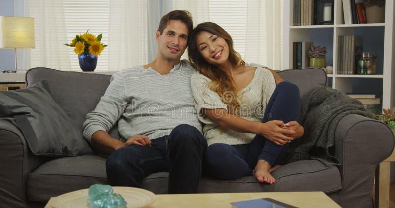 Attraktive Mischrassepaare, die auf dem Couchlächeln sitzen lizenzfreies stockfoto