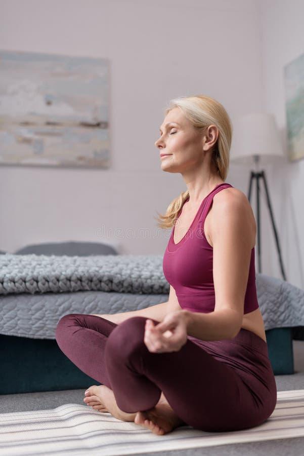 attraktive mittlere Greisin, die in Lotussitz auf Yogamatte sitzt lizenzfreie stockfotografie