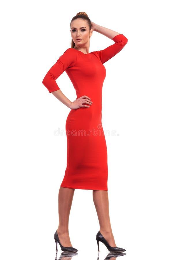 Attraktive Modefrau, die ein dünnes rotes Kleidergehen trägt stockfoto
