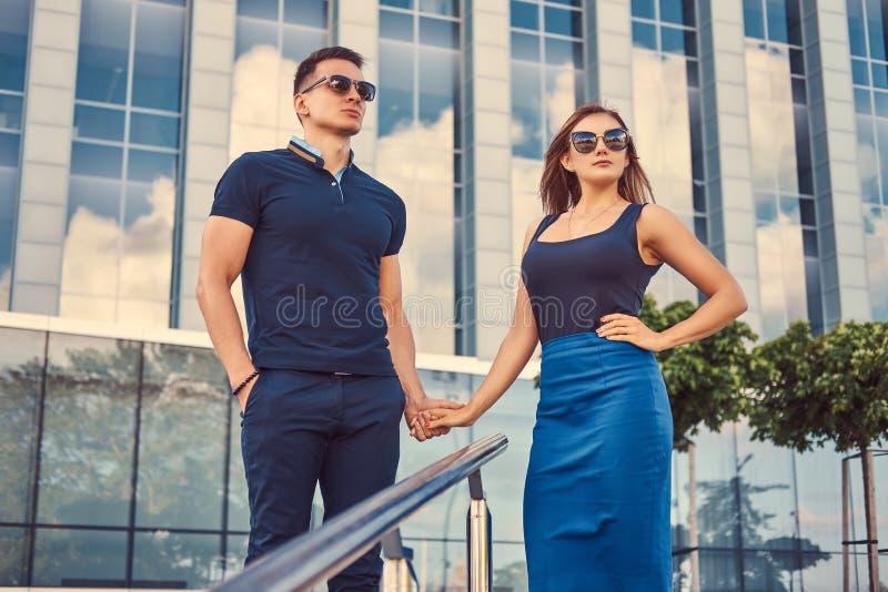 Attraktive moderne Paare, sexy blondes Mädchen und gutaussehender Mann, die in der modernen Stadt gegen einen Wolkenkratzer steht stockbilder