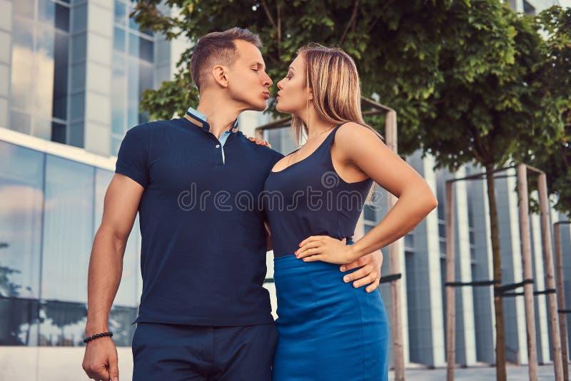 Attraktive moderne Paare, sexy blondes Mädchen und gutaussehender Mann, die in der modernen Stadt gegen einen Wolkenkratzer steht stockfotografie