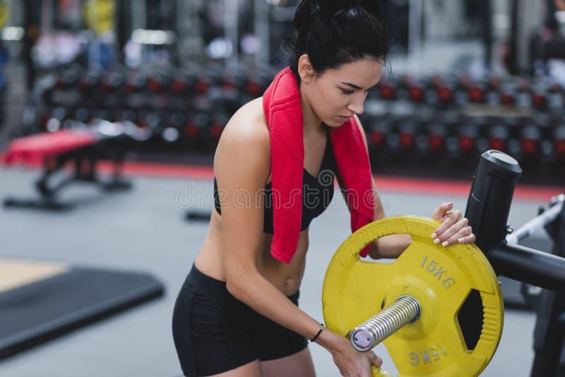 Attraktive muskulöse junge Frau, die Training in der Turnhalle, anhebende Gewichte mit Barbell tut Leute, Sport, Eignungskonzept lizenzfreie stockbilder