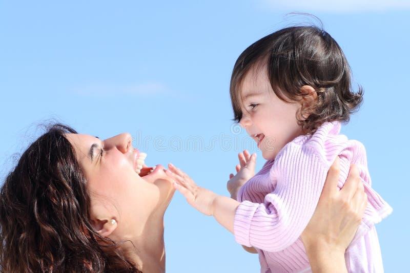 Attraktive Mutter, die ihre Tochter aufzieht und zusammen spielt stockbilder