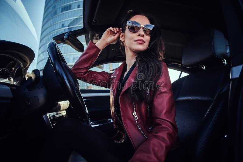 Attraktive nachdenkliche Frau in der roten Jacke und in der Sonnenbrille wirft in ihrem Auto auf stockbild