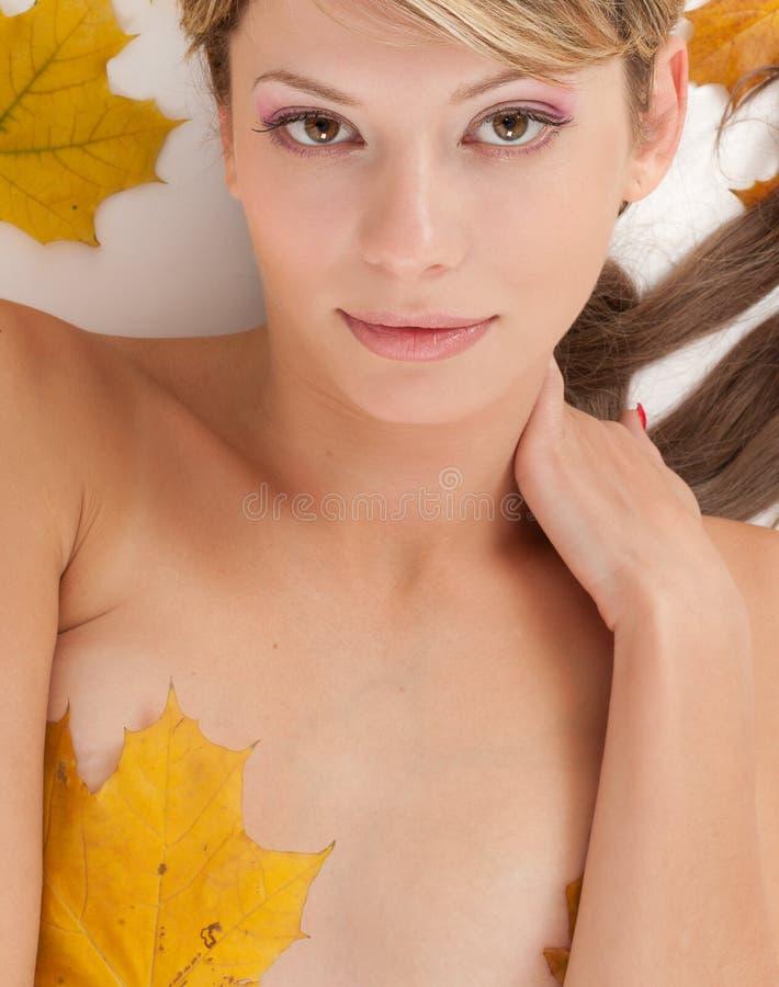 Attraktive Nacktheitfrauenbedeckung durch Ahornholzblätter stockbilder