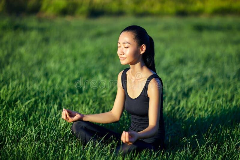 Attraktive orientalische Frau, die auf Gras in der Meditation sitzt stockbilder