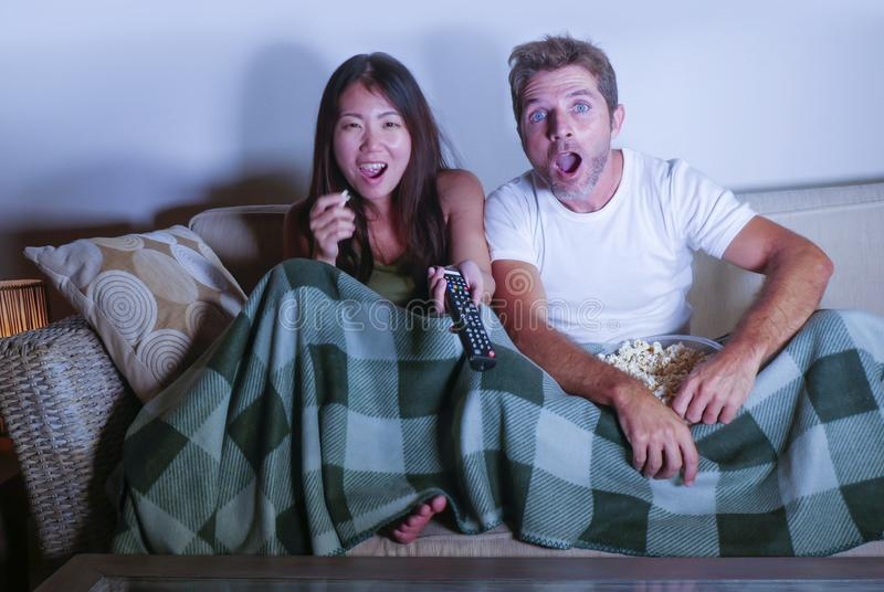 Attraktive Paare der jungen Mischrasse mit asiatischer koreanischer Frau und weißen dem Mann, die den Fernseh, genießt komödienfi lizenzfreie stockfotos