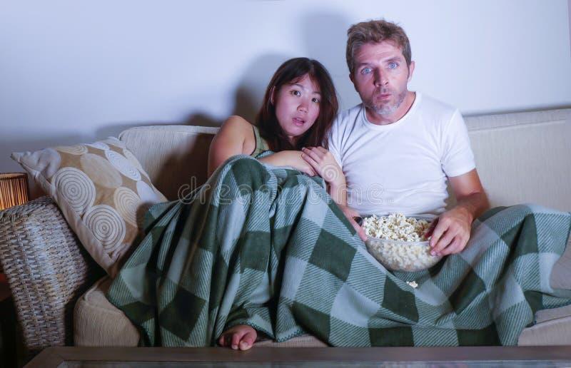 Attraktive Paare der jungen Mischrasse mit asiatischer koreanischer Frau und weißen dem Mann, die Fernseh, genießt Horrorfilm im  lizenzfreie stockbilder