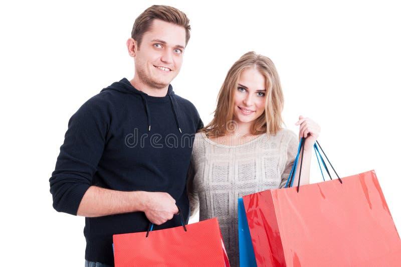 Attraktive Paare, die Bündel Einkaufstaschen halten stockbild