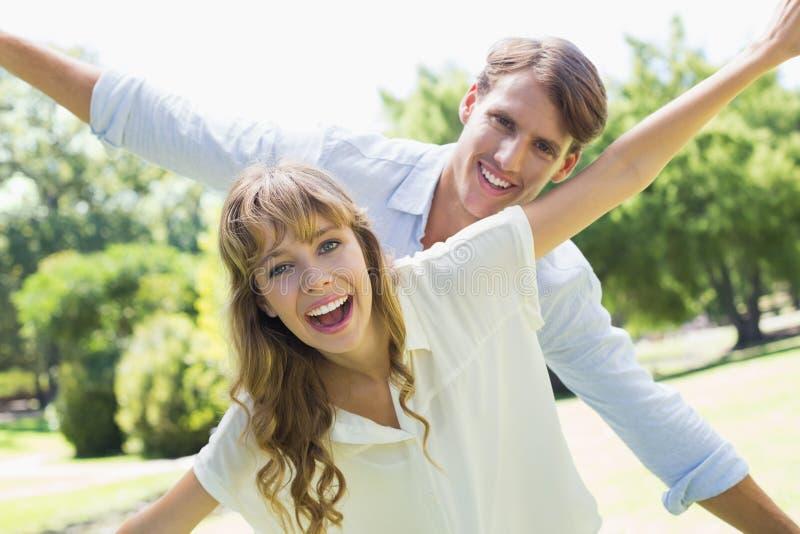 Attraktive Paare, die an der Kamera und an ausgebreiteten Armen im Park lächeln lizenzfreie stockfotos