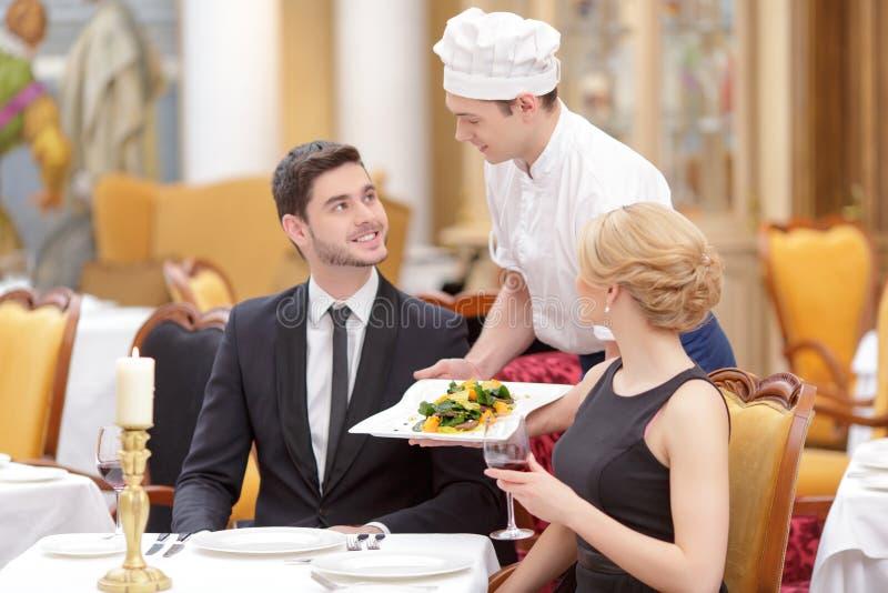 Attraktive Paare, die Luxusrestaurant besichtigen lizenzfreie stockbilder