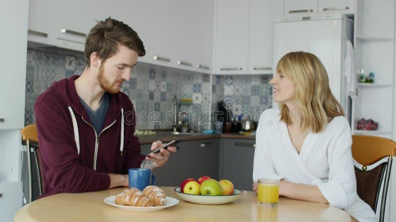 Attraktive Paare, die zusammen zu Hause in der Küche frühstücken stockfotografie