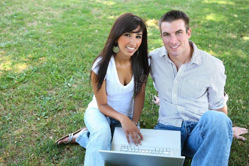 Attraktive Paare im Park mit Laptop lizenzfreie stockfotografie