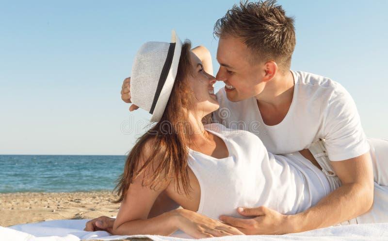 Attraktive Paare am Strand lizenzfreie stockbilder