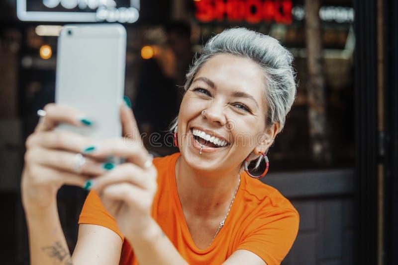 Attraktive positive Blondine im orange T-Shirt, das selfie am Café macht stockfotos