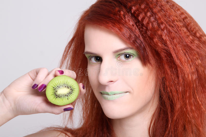 Attraktive redhaired Frau mit Kiwi über Weiß stockfoto
