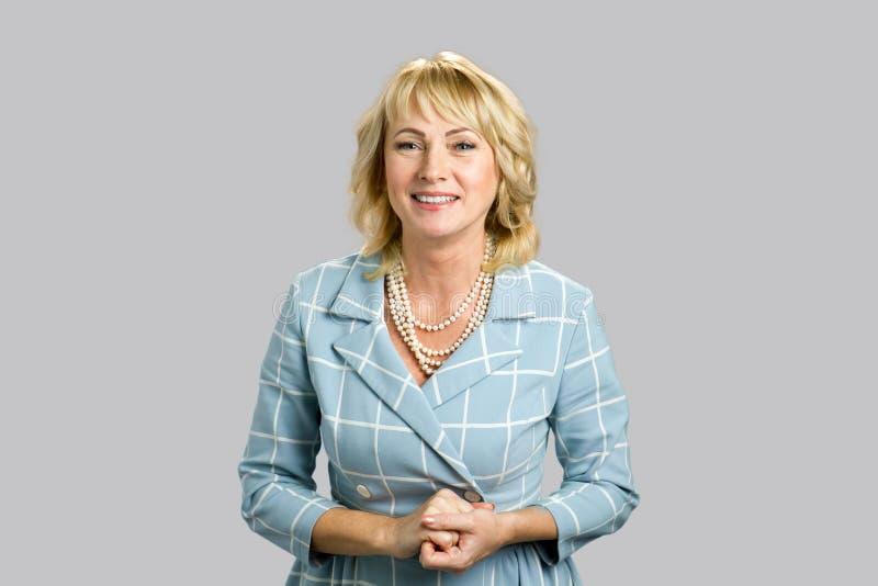 Attraktive reife Frau auf grauem Hintergrund lizenzfreies stockbild