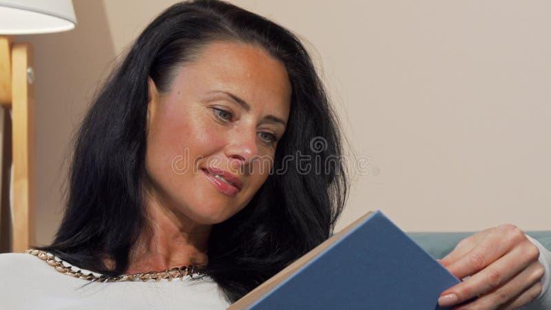 Attraktive reife Frau, die interessantes lächelt Buch froh, lesend stockfoto