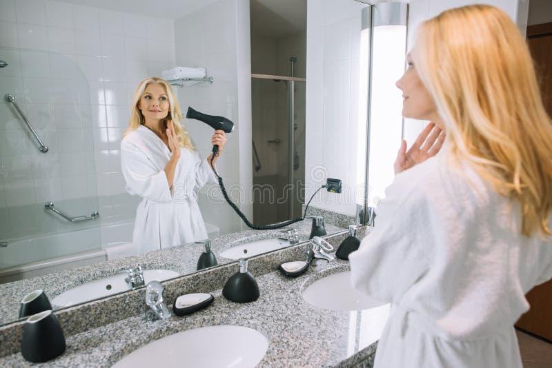 attraktive reife Frau in trocknendem Haar des Bademantels mit Haartrockner im Badezimmer stockfotografie