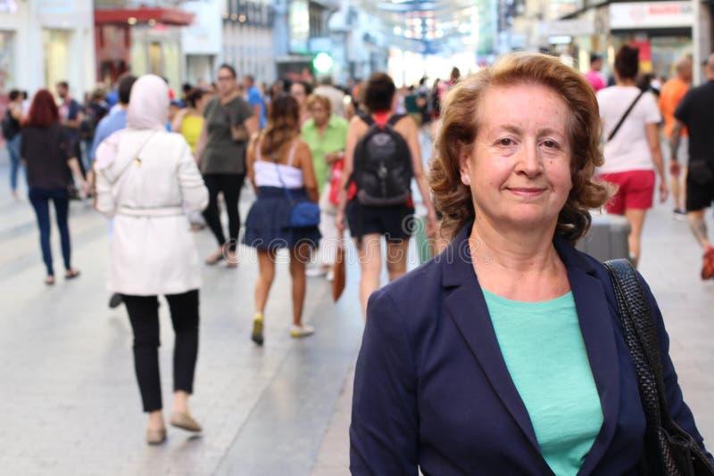 Attraktive reife Greisin gegen beschäftigte Stadtstraße mit vielen Leute- und Kopienraum stockfotografie