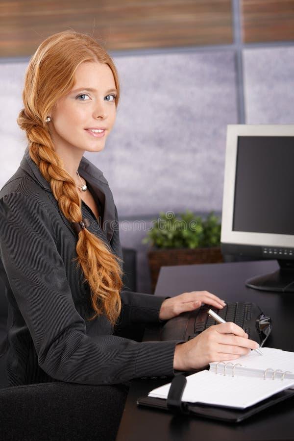 Attraktive Rothaarigegeschäftsfrau bei der Arbeit lizenzfreie stockfotografie