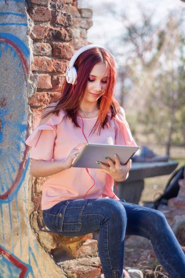 Attraktive Rothaarigen weiblich mit der digitalen Tablette, die Musik auf Kopfhörern auf Ruinenwandziegelsteinen des Retro- Hause lizenzfreies stockfoto