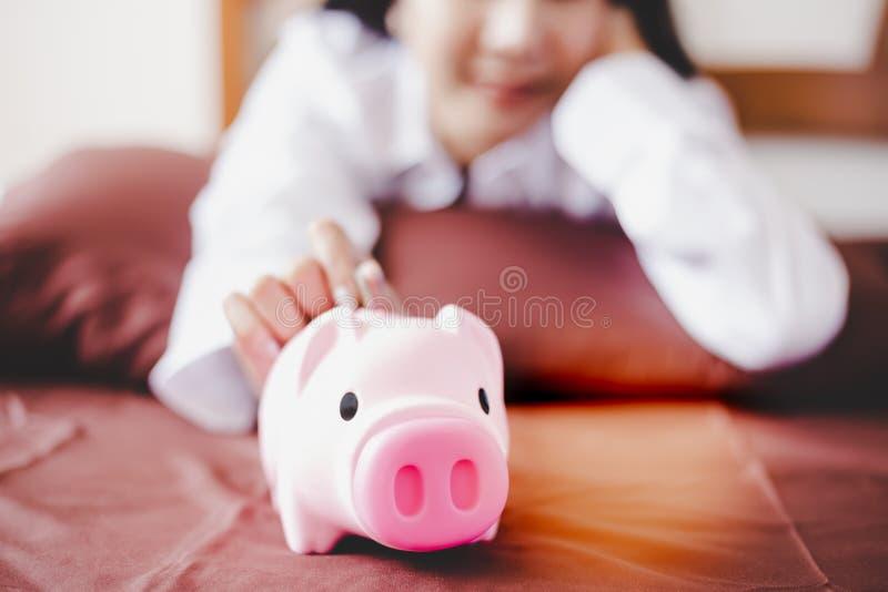 Attraktive Schönheit setzt eine Münze zum Sparschwein Bezaubernde schöne asiatische Frau immer spart und speichert lizenzfreie stockfotografie