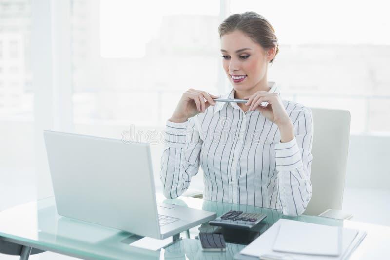 Attraktive schicke Geschäftsfrau, die einen Bleistift sitzt an ihrem Schreibtisch hält lizenzfreie stockfotos