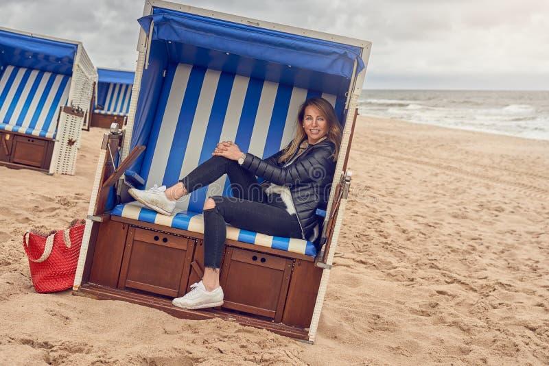 Attraktive schlanke blonde Frau, die in einer Strandhütte sitzt lizenzfreies stockfoto