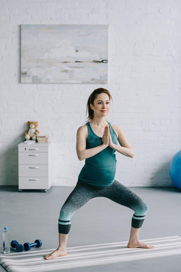 attraktive schwangere Frau, die in Yogaposition steht stockfotografie