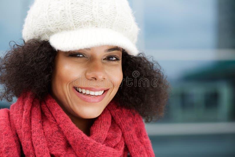 Attraktive schwarze Frau, die mit Winterhut und -schal lächelt stockfoto
